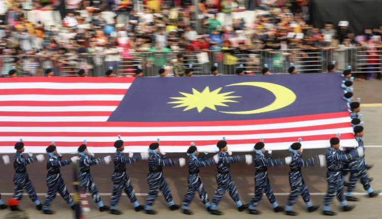 Youths in the National Service uniform carry the Jalur Gemilang during the parade for the Merdeka Day celebration at Dataran Merdeka, Kuala Lumpur on Aug 31, 2017. — Sunpix by Ashraf Shamsul