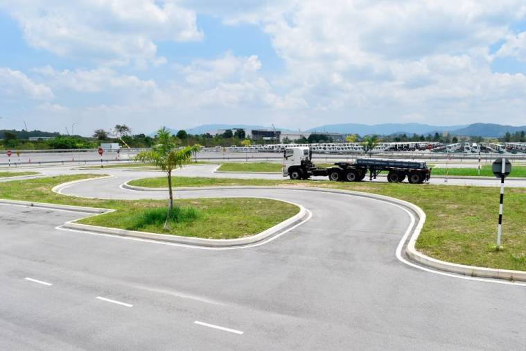 A Hino 500 Series medium duty lorry going through a series of narrow, sharp turns and obstacles at the HTSCC test track.
