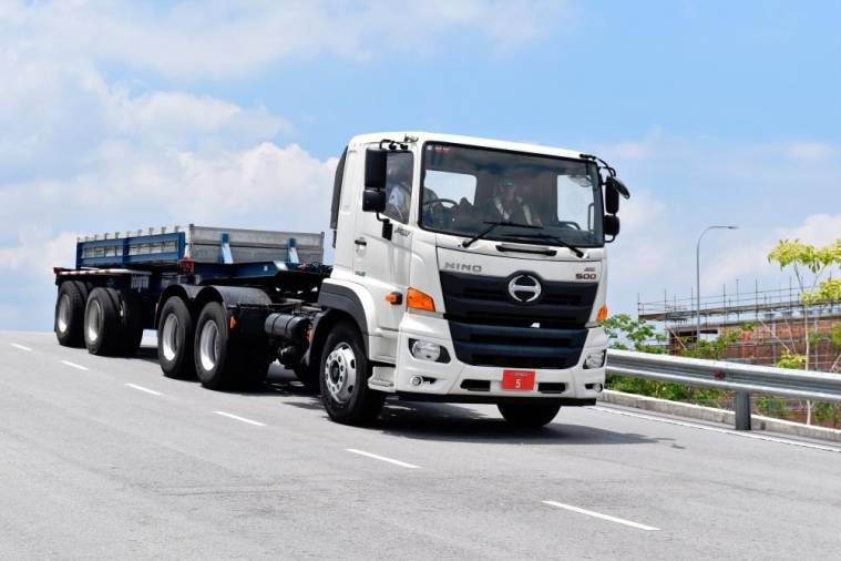 A Hino 500 Series medium duty lorry goes up and down a steep slope at the HTSCC test track, while carrying a 10-tonne load on its trailer.