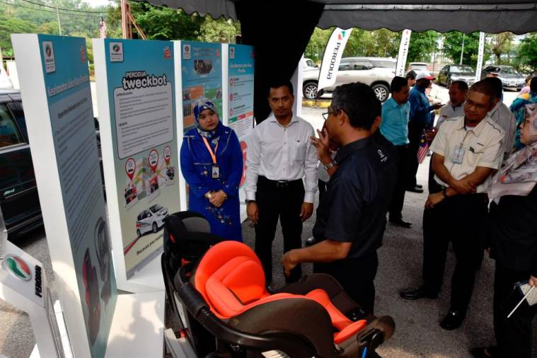 $!Hulu Selangor district council (MDHS) president Shukri Mohamad Hamin being taken on a tour of Perodua's safety booth at the launch of MDHS' 'Fly the Jalur Gemilang' campaign, yesterday.