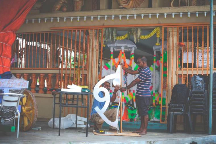 M Mohana Sundaram and his assistant K. Balu making a frame for kavadi by using polysterene.