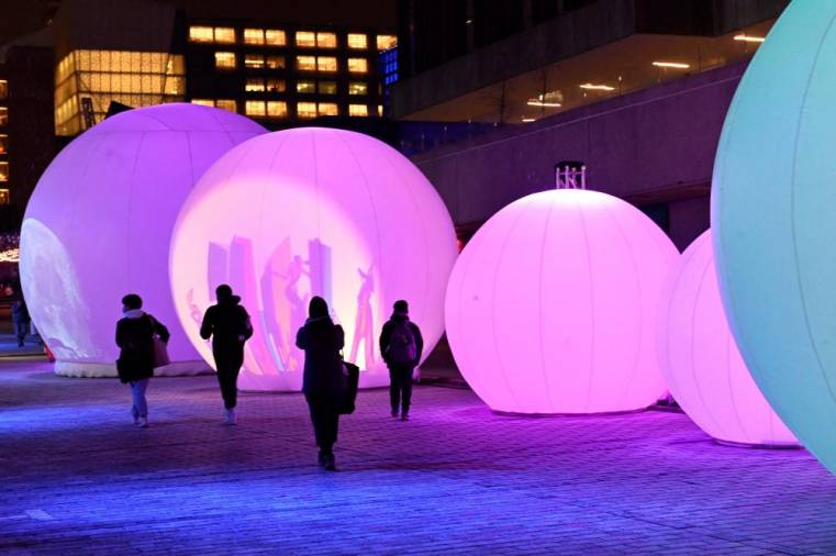 People enjoy the 'New Moon' sound-and-light installation, consisting of seven inflated spheres that reveal through shadows and light, iconic images and stories inspired by the culture of the Quartier des Spectacles, on December 14, 2020 in Montreal, Quebec, one of the five light installations on display to bring some comfort to residents of a city that has been battered by months of coronavirus. AFP / Eric THOMAS