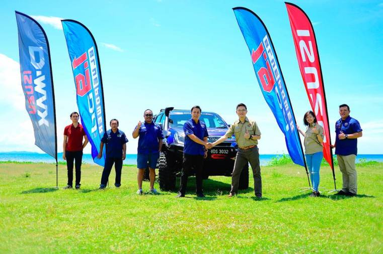 $!Isuzu Malaysia marketing manager Alan Lee (3rd from right) hands over the 'Blue Monster' to the president of the Sabah Four-Wheel-Drive Association Faez Nordin (4th from left).