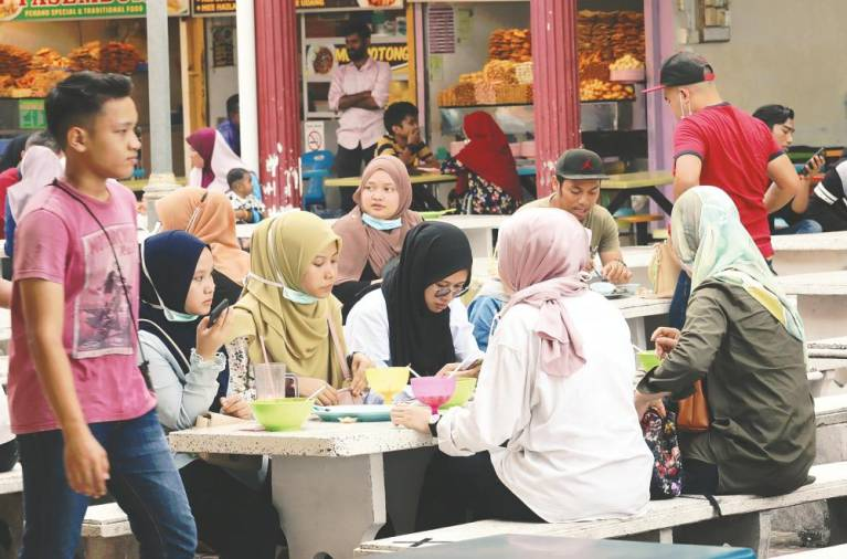 NO SOP? ... These youngsters seem to have thrown caution to the wind, ignoring the requirement for social distancing as they dine in the open at an eatery in Padang Kota, George Town yesterday. – MASRY CHE ANI/THESUN