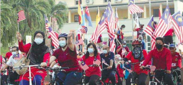 PATRIOTIC ON WHEELS... Staff of Penang Teacher Training Institute training for the Aug 18 Merdeka Ride in George Town. The event, held in conjunction with the National Month celebrations, will take 150 Jalur Gemilang-bearing cyclists through several historical sites near the Penang Bridge. MASRY CHE ANI/THE SUN