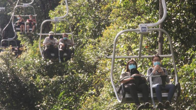 FUN TIME... Visitors to Escape Penang in Teluk Bahang enjoy cable car rides as the theme park reopens after nearly three months due to the movement control order. However water activities are still not allowed. MASRY CHE ANI/THE SUN
