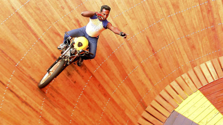Stuntmen from Sri Lanka, Sugth and Nimal perform stunts on motorcycles inside the cylinder cone called 'Wall of Death'.