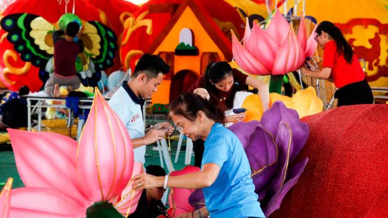 Volunteers work on a Lunar New Year festive lantern as part of the decorations in preparation for the Lunar New Year at FGS Dong Zen Temple in Jenjarom. Asyraf Rasid / the sun