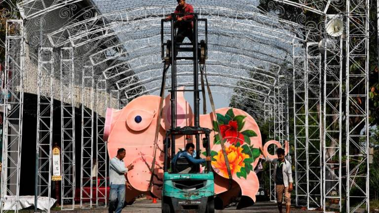 Workers use a forklift to lift a pig shaped decor item in preparation for the Lunar New Year at FGS Dong Zen Temple in Jenjarom. Asyraf Rasid / the sun