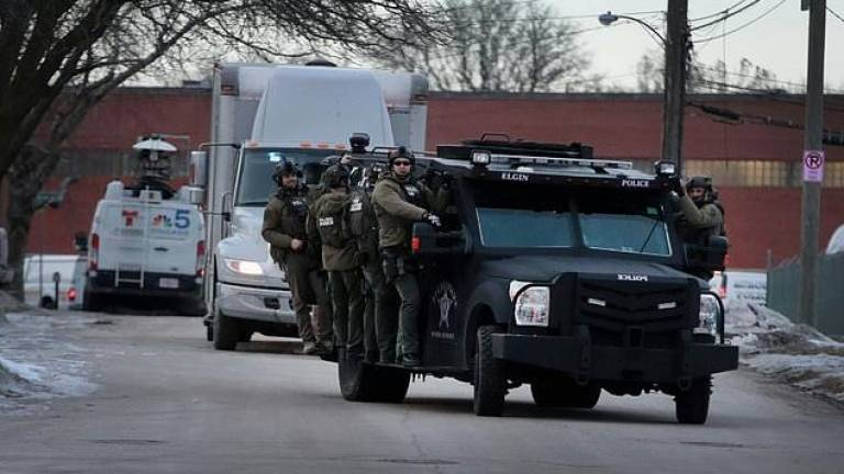 Police secure the area following a shooting at the Henry Pratt Company in Aurora, Illinois. — AFP
