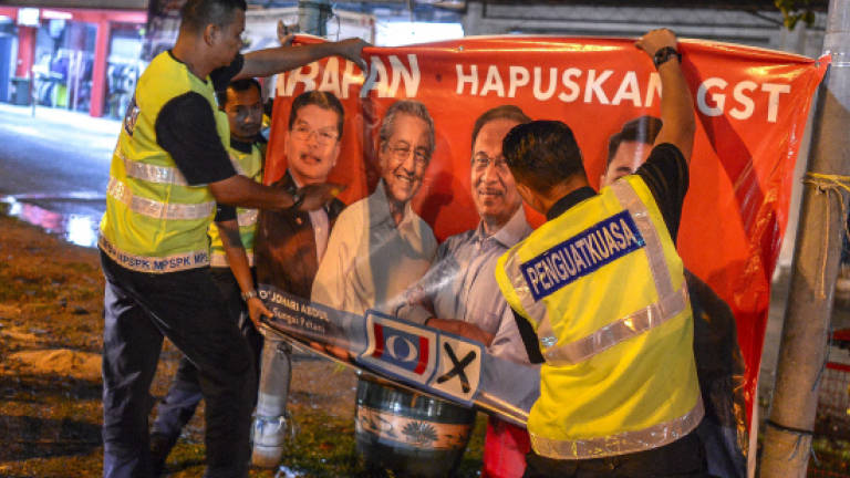 EC officers remove images of Tun M in midnight operation