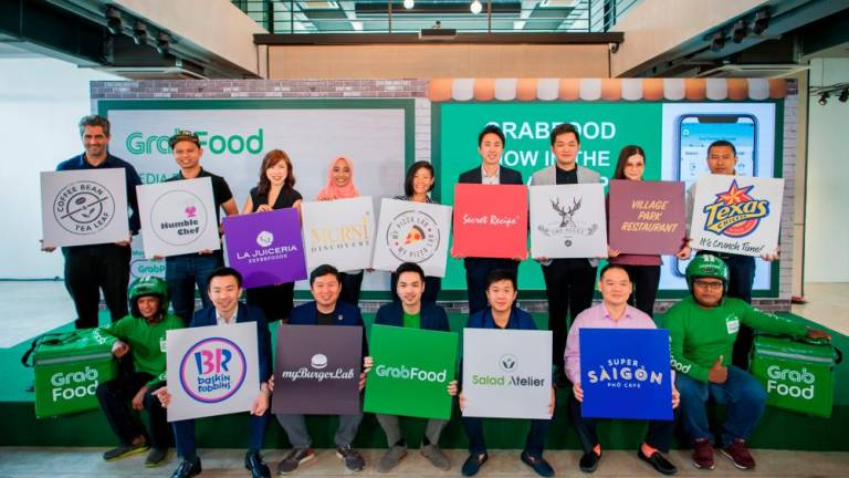 Goh (seated, in the middle) with GrabFood merchant partners.