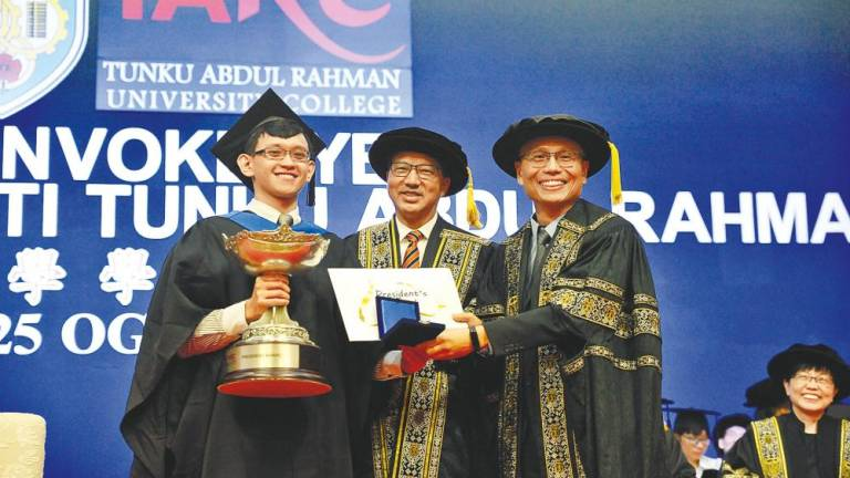 Prof Dr Lee Sze Wei (right), President of TAR UC, presenting the trophy, certificate and token of appreciation to Ong Kevin (left), the President's Award winner while Liow witnesses the exchange.