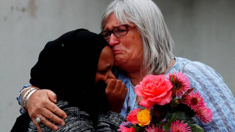 Women embrace near Masjid Al Noor mosque in Christchurch, New Zealand.