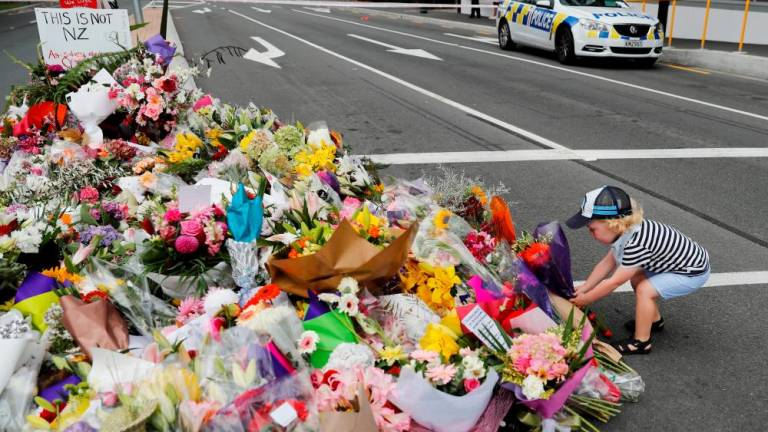 A boy places flowers at a memorial as a tribute to victims of the mosque attacks, near a police line outside Masjid Al Noor in Christchurch, New Zealand.