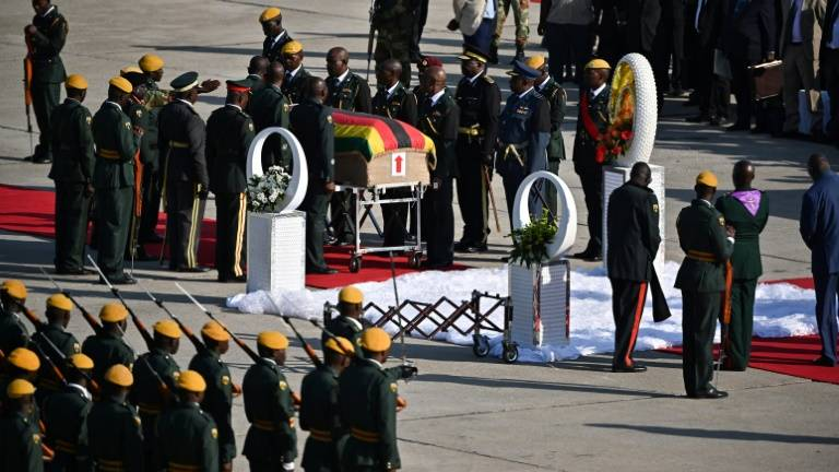 Mugabe's body arrives home to divided Zimbabwe, burial dispute