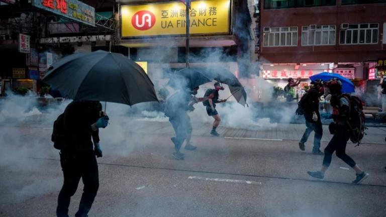 Tear gas and water cannon as Hong Kong crowds defy rally ban