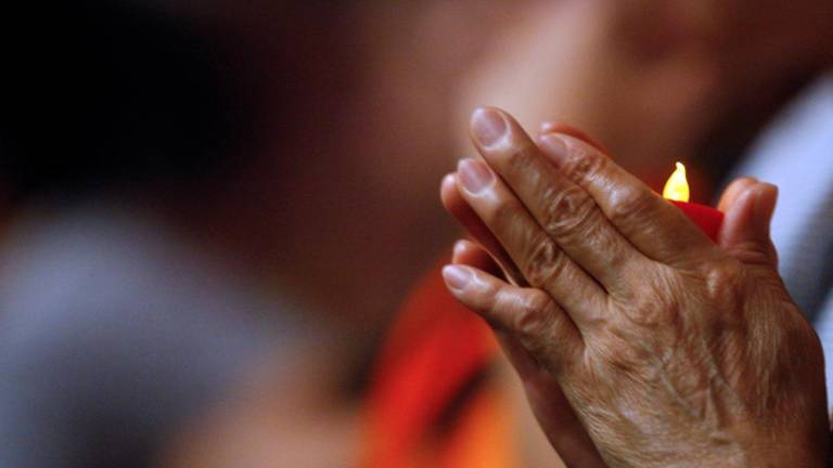 A Malaysian Buddhist offer prayers during a mass prayer for flight MH370 in Wisma MCA, Kuala Lumpur.