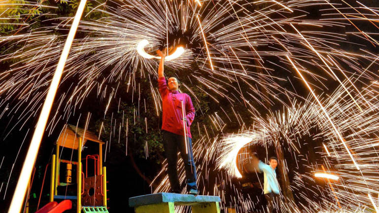 A Muslim man uses a soft brush to produce sprinkler fireworks ahead of the Eid al-Fitr celebrations outside Kuala Lumpur on July 27, 2014.