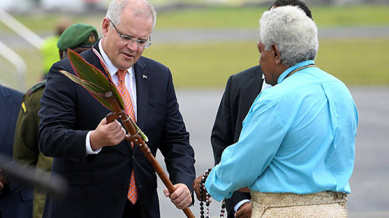 Australian Prime Minister Scott Morrison is presented with a gift as he arrives in Port Vila, Vanuatu — Reuters