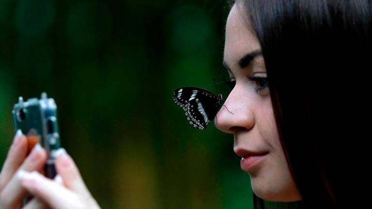 Oksana Babinova takes a selfie with a butterfly at the Kuala Lumpur Butterfly park.