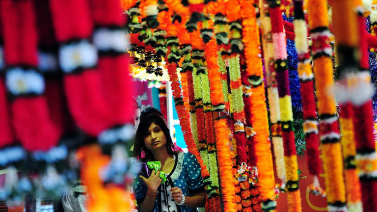 A girl walks past colourful flowers at Little India in Brickfields.