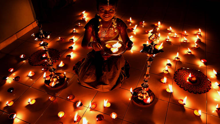 "Seven year old M. Rinashini Venila, holds an earthen lamp while decorating an area of her house to celebrate Diwali at Setapak on October 18, 2014. Diwali also known as Deepavali and the ""festival of lights"", an ancient Hindu festival celebrated in autumn every year. The festival spiritually signifies the victory of light over darkness, knowledge over ignorance, good over evil, and hope over despair."