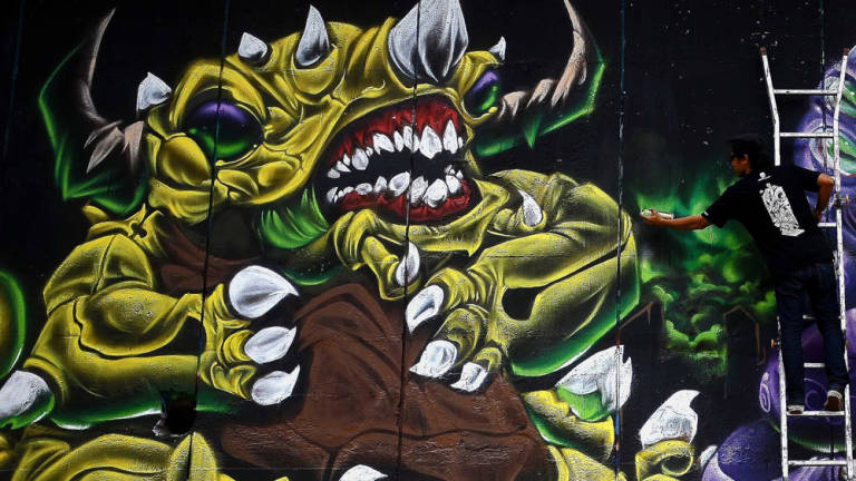 Graffiti featuring the giant monster during a 'Separation 2 Giant Shall Rise 2014 Graffiti' at the Sungai Klang riverbank wall near Pasar Seni in Kuala Lumpur.