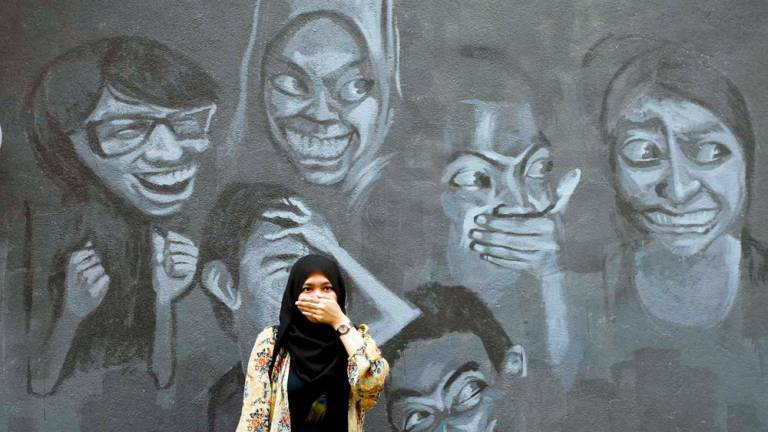 A women poses at a cartoon wall during the launch of the art site in Shah Alam.