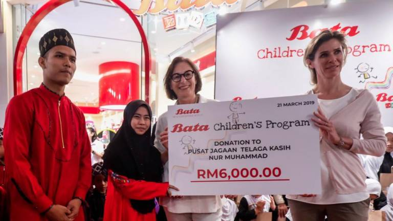 Bata Global board members Christine Schmidt (left) and Miriam Staub Bisang presenting the mock cheque to representatives from the orphanage. — Sunpix by Ashraf Shamsul