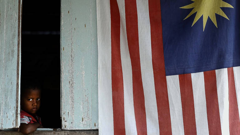 A child peers out during a ministerial visit to Kampung Sungai Judah, Pulau Carey organised by the Malaysian Communications and Multimedia Commission.