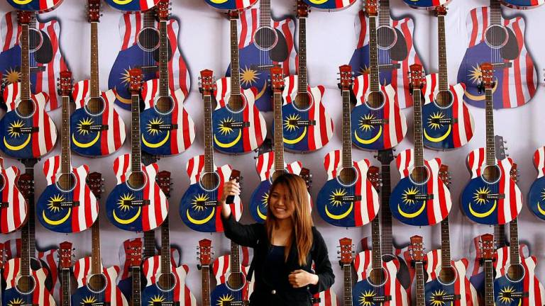 Leu Eevone take a selfie with 57 Jalur Gemilang guitars at the MCA building.