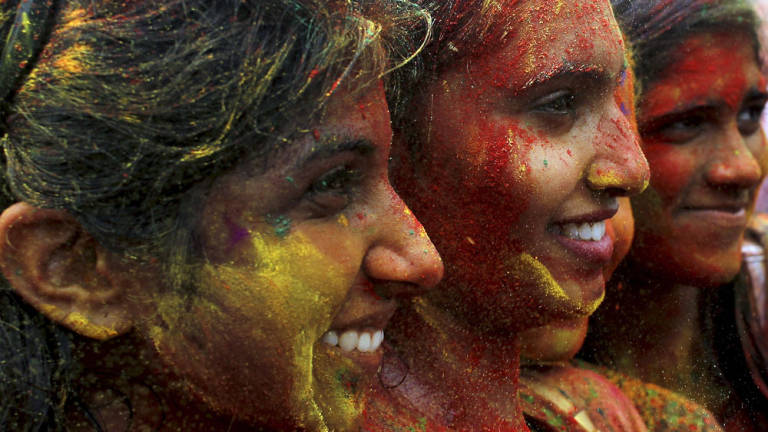 Participants of the Holi festival have their faces splattered with different colours at the Shree Lakshimi Narayan Temple. — Sunpix by Asyraf Rasid