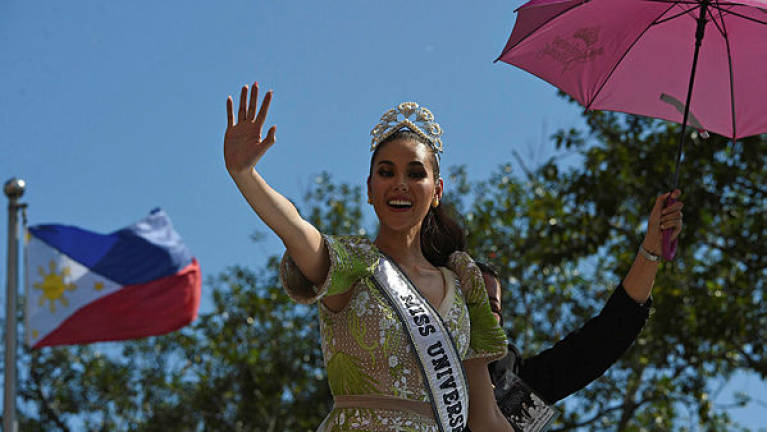 Miss Universe 2018 Catriona Gray of the Philippines waves to fans during a parade held in her honour in Manila — AFP