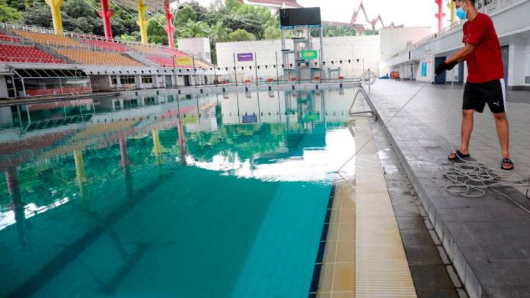 Technician Darul Ehsan Facilities Management Sdn Bhd is doing pool maintenance at Darul Ehsan Aquatic Center. ASYRAF RASID / THE SUN