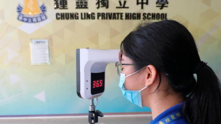 A staff at SMK Chung Ling (Independent) Loo Jee Ying conducting an inspection on body temperature equipment as preparation for the school resumption of Form 5 and Form 6. MASRY CHE ANI/THE SUN