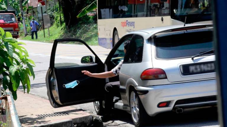 A passenger throws a face mask out of the car in blatant disregard for hygiene and cleanliness in a suburb in George Town yesterday. – MASRY CHE ANI/THESUN