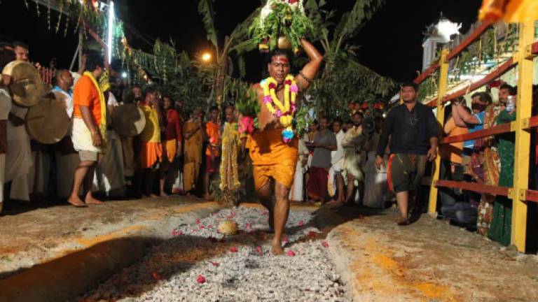 Hindu devotees take part in fire-walking ceremony in Air Itam