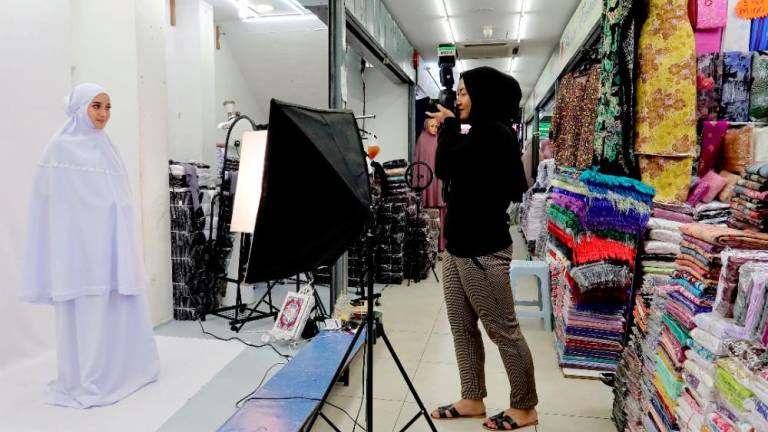 A female photographer doing a photo session with a model at a small studio at Jalan Tuanku Abdul Rahman, Kuala Lumpur. ZAHID IZZANI/THESUN