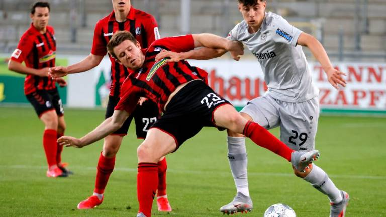 Freiburg's Dominique Heintz (2nd left) in action with Bayer Leverkusen's Kai Havertz (right) during the German Bundesliga match at Schwarzwald-Stadion, Freiburg, Germany on May 29, 2020. – REUTERSPIX