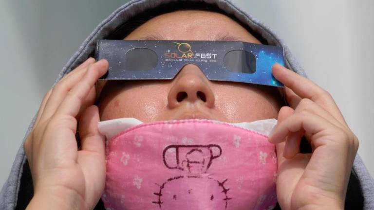 A women, wearing a protective face mask against the coronavirus disease (COVID-19), uses special protective glasses to watch a partial solar eclipse at Planetarium Negara . ASYRAF RASID/THESUN