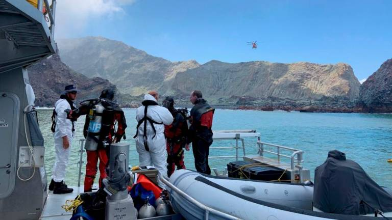 New Zealand divers search contaminated waters for volcano victims