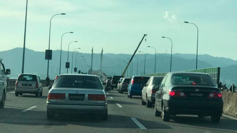 A crane is used in an attempt to retrieve the white SUV which crashed off the Penang Bridge on Jan 19, 2019.