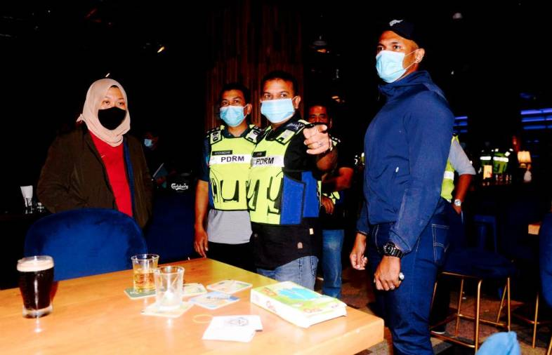 $!SPOT CHECK ... Johor police chief Datuk Ayob Khan Mydin Pitchay (third from left) with personnel from the district municipal council jointly conducting a raid on an entertainment outlet in Johor Baru yesterday.