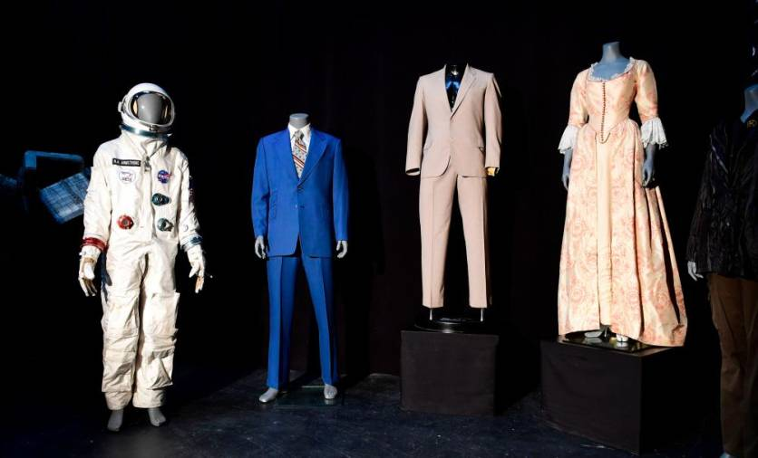 "Items up for auction at the Prop Store Auction in late August are on display July 15, 2020, at the Prop Store in Valencia, California, including from (L-R), Neil Armstrong's spacesuit worn by Ryan Gosling in the film ""First Man"", the Blue suit worn by Will Farrell in the film ""Anchorman"", a suit worn by Al Pacino in the film ""Godfather 2"", and a dress worn by Keira Knightly in the film ""Pirates of the Caribbean."" / AFP / Frederic J. BROWN / TO GO WITH AFP STORY by Ben SHEPPARD -- ""'Top Gun' helmet and 'Alien' spaceship in Hollywood props auction"""