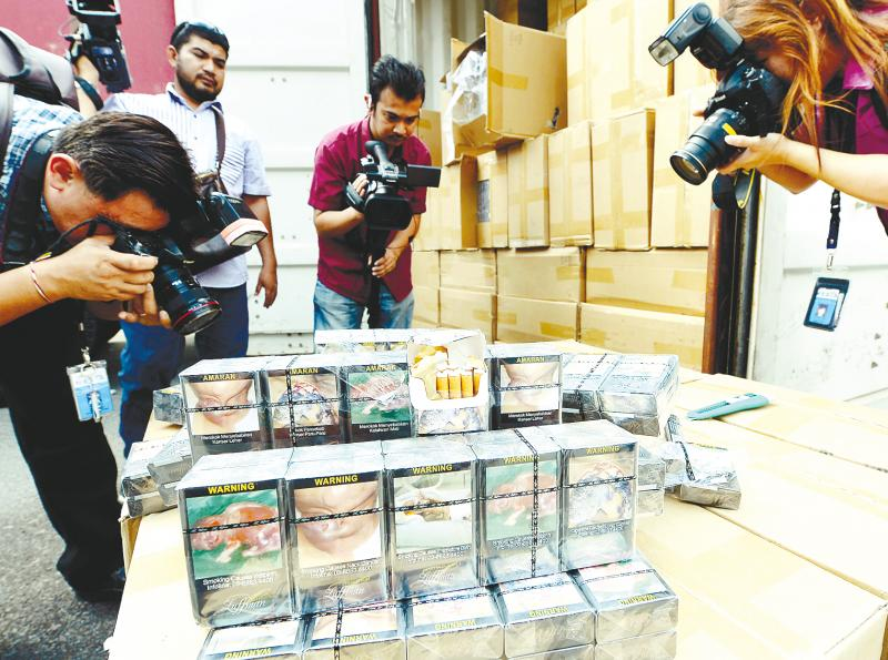 Press photographers taking pictures of part of 40,000 cartons of illegal cigarettes seized at the KL International Airport. — Bernama