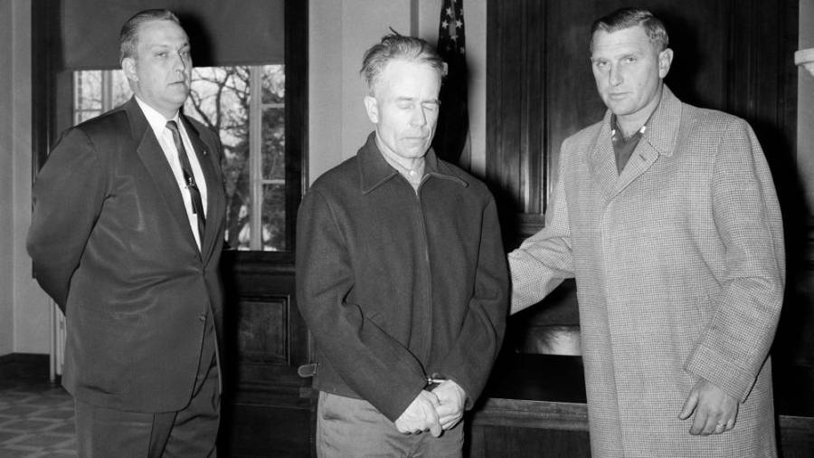 The butcher of Plainfield, Ed Gein (C) being led to his first court appearance by investigators.