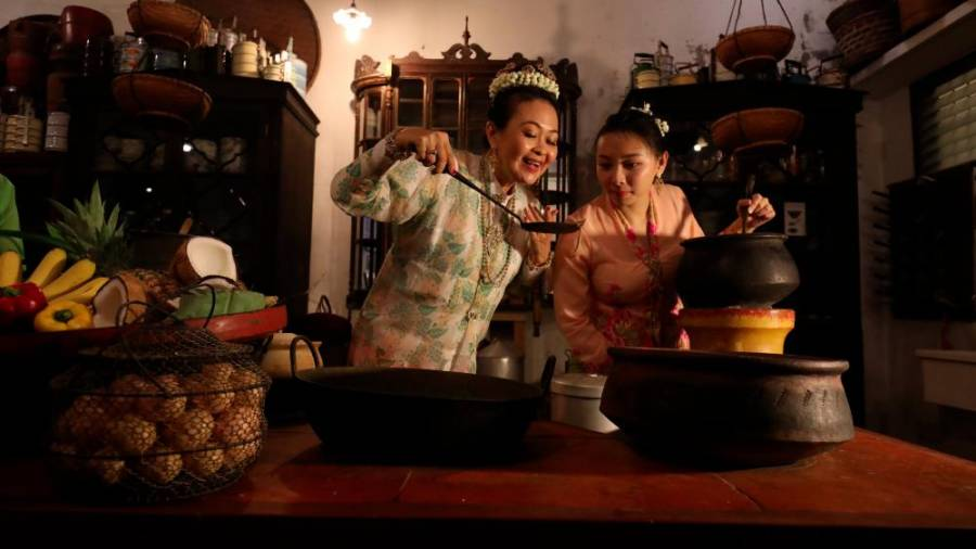 Lilian Tong and Cheng Hooi Yen whipping up traditional nyonya dishes.