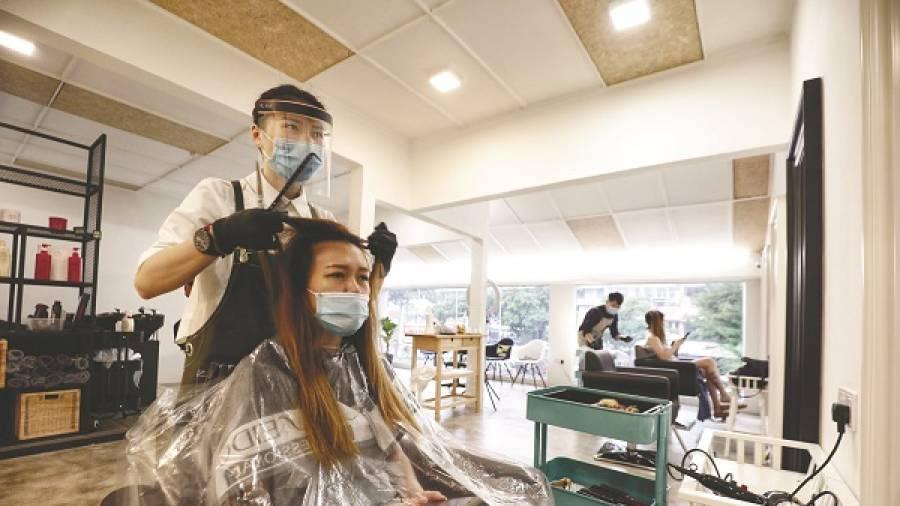 $!BACK IN BUSINESS ... A stylist cutting a client's hair in a salon in Petaling Jaya, after hairdressers were allowed to resume business under the recovery movement control order. – Zahid Izzani/TheSun