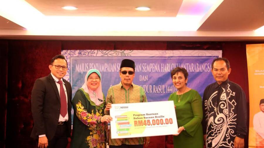 Silatul (third from left) receives a mock cheque from Nirmalah (second from right).